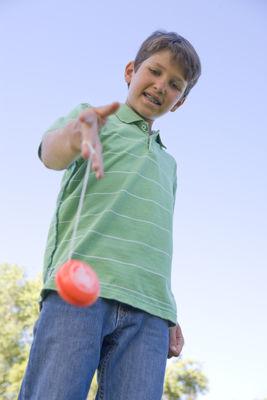 Young Boy Using Yo Yo Outdoors Smiling