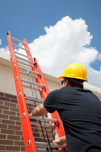 Construction Worker Climbing A Ladder Up To The Roof