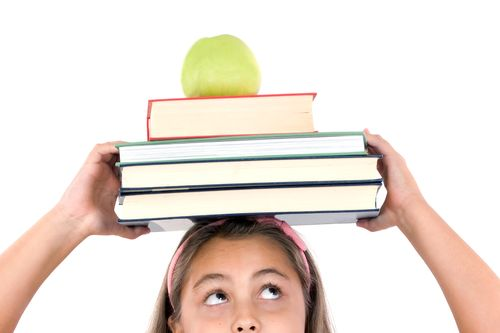 Adorable Girl Studying With Books And Apple In The Head