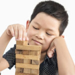 Asian Kid Is Playing Jenga A Wood Blocks Tower Game For Practicing Physical And Mental Skill