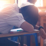Asian Woman Student Sleep On The Table In Classroom