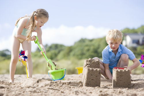 Brother And Sister At Beach Making Sand Castles
