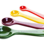Ceramic Measuring Spoons In Four Bright Colors Shot On White Background