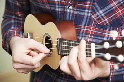 Close Up Of Man Playing Ukulele