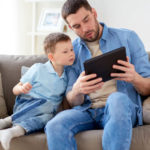 Family Fatherhood Technology And People Concept Happy Father And Little Son With Tablet Pc Computer Sitting On Sofa At Home Father And Son With T