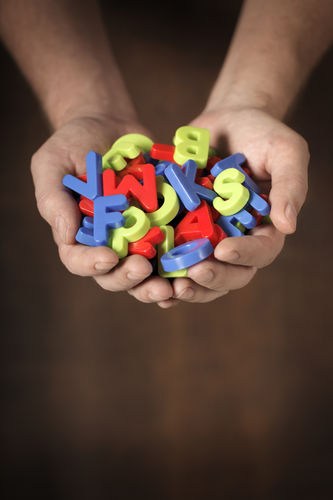 Man Holding Colorful Plastic Toy Letters In His Hands
