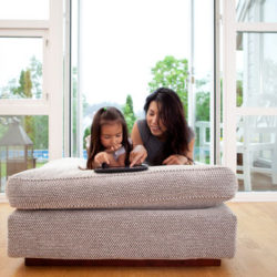 Mother And Young Daughter Using A Digital Tablet In A Living Room Interior