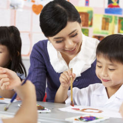 Teacher Helping Students During Art Class In Chinese School Classroom