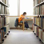 Teenage Boy Doing Homework In Library