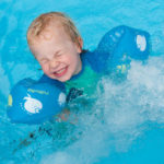 Young Child Swimming With Arm Bands And Being Splashed