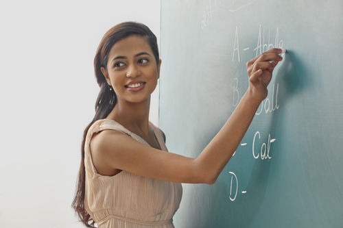 Young Female Teacher Writing On Green Board While Looking Away