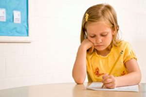 Young Girl In Classroom Writing On Paper