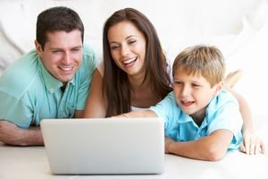 Young Parents With Child On Laptop Computer